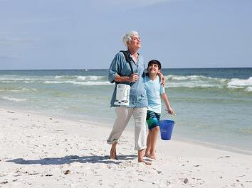 Woman walking on the beach with her grandson.