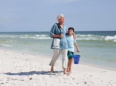 Woman walking with portable oxygen concentrator.
