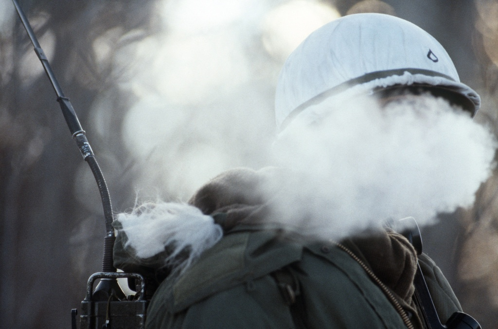 A radio operator's breath mixes with the cold Alaskan air to form a steam cloud temporarily shielding his face during Exercise BRIM FROST'87