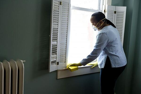 Woman cleaning a window sill.