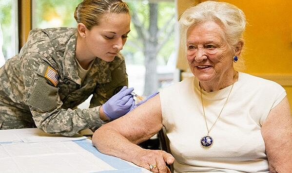 Woman in military uniform giving shot to woman.