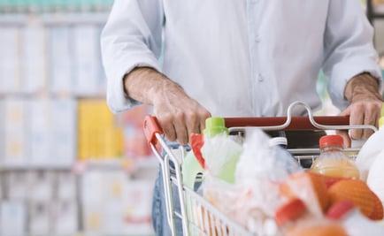 Man pushing shopping cart in a grocery store.
