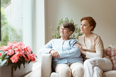 Old woman and caretaker sitting on a couch looking out a window.