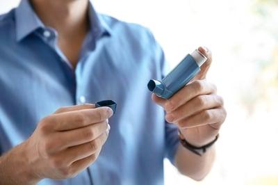 Man in blue shirt holding an inhaler.