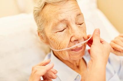 Caregiver adjusting woman's nasal cannula.