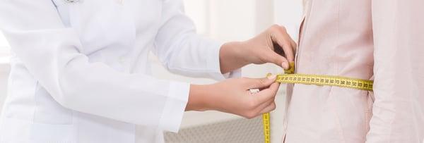 Doctor measuring a patient's waistline.