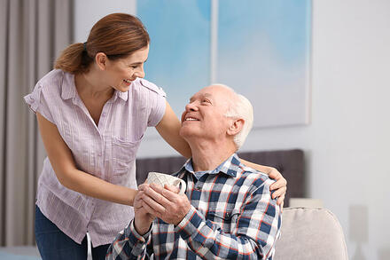 Caregiver smiling at man with a cup of coffee.