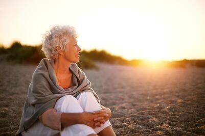 Woman sitting on a beach watching the sunset.