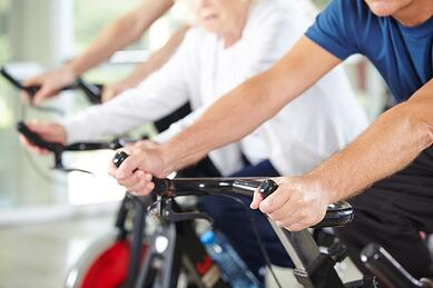 Men and women exercising on stationary bikes.