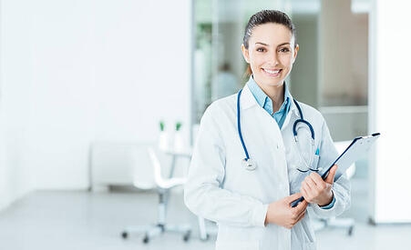 Doctor smiling while holding a clipboard.