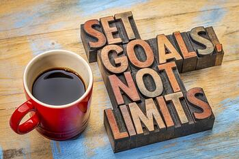 "Coffee mug and sign that says ""set goals not limits."""