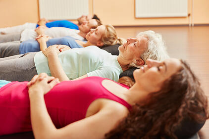 Group of people practicing breathing exercises.