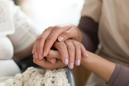 Caregiver and patient holding hands.