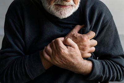 Elderly man holding his chest.