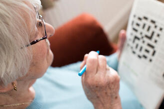 Old woman doing a cross word puzzle.