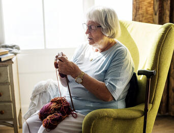 Woman sitting in a chair knitting.