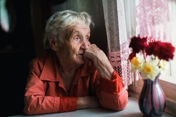 Old woman looking out a window.
