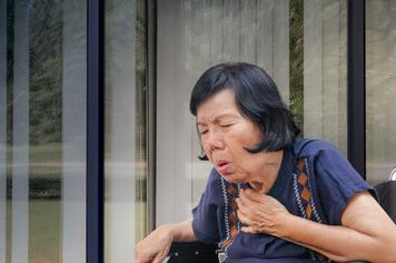 Woman coughing with hand on chest.