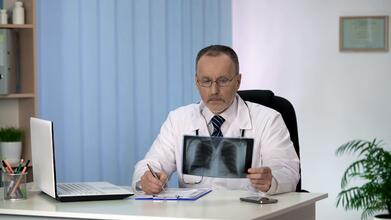 Pulmonologist looking at lung X-rays.