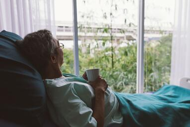 Woman laying in bed looking out the window.