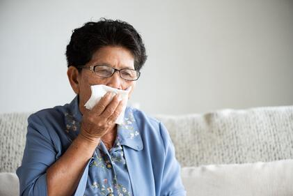 Woman coughing in a napkin