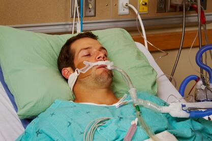Man in bed with ventilator