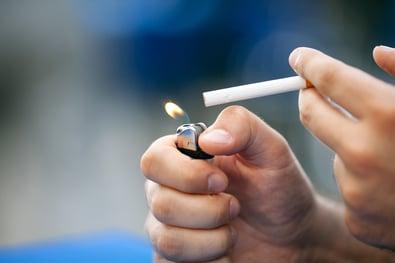 Man lighting a cigarette.