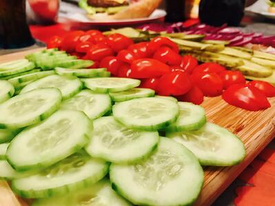 Cucumbers and tomatoes on a cutting board.