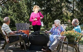 Woman with portable oxygen concentrator speaking to friends.