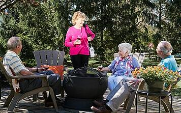Woman with oxygen concentrator speaking with friends.