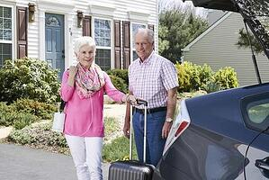 Man and woman standing with portable oxygen concentrator