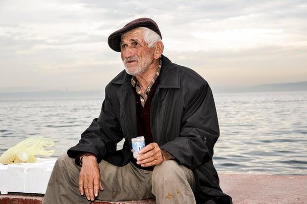 Man sitting near a body of water.