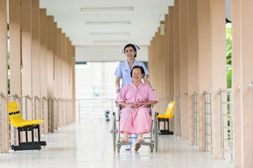 nurse pushing woman in wheelchair.