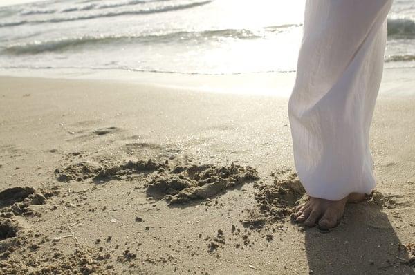 Woman standing on a beach.
