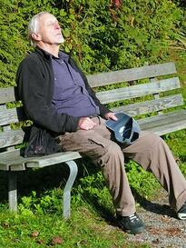Man experiencing heat exhaustion sitting on a bench.