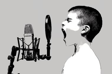 Boy singing into a microphone.