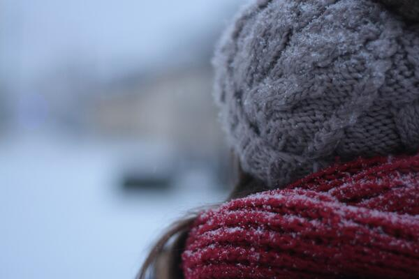 Woman standing in the cold with a wool scarf.