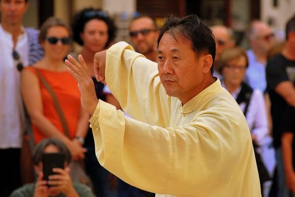 Man in yellow robe doing Tai Chi.
