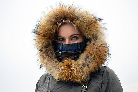 Woman standing in the cold with a heavy jacket on.